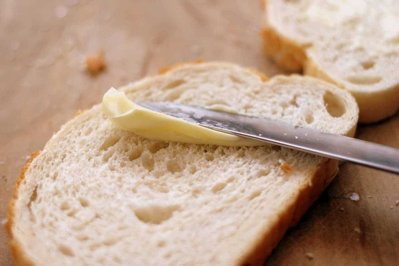 White bread with margarine being spread on it - this is one of may foods that can be harmful to people with acne