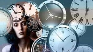 Picture of female adult surrounded by clocks to depict the dilemma of the clocks going forward
